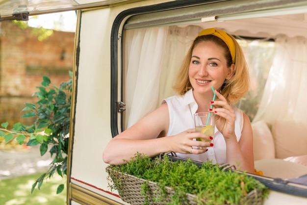 Kobieta trzyma szklankę lemoniady w przyczepie kempingowej