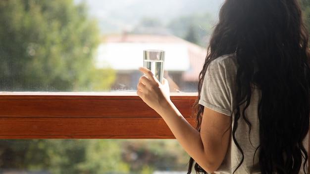 Kobieta trzyma szklankę wody z tłem okna