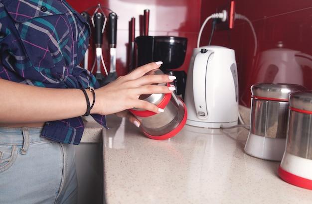 Kobieta trzyma szklany słoik cukru w kuchni.
