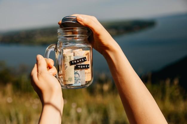 Kobieta trzyma szklany słoik z pieniędzmi