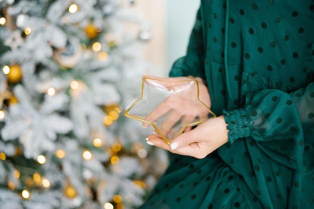 Kobieta trzyma szklany talerz w kształcie gwiazdy. zbliżenie dłoni