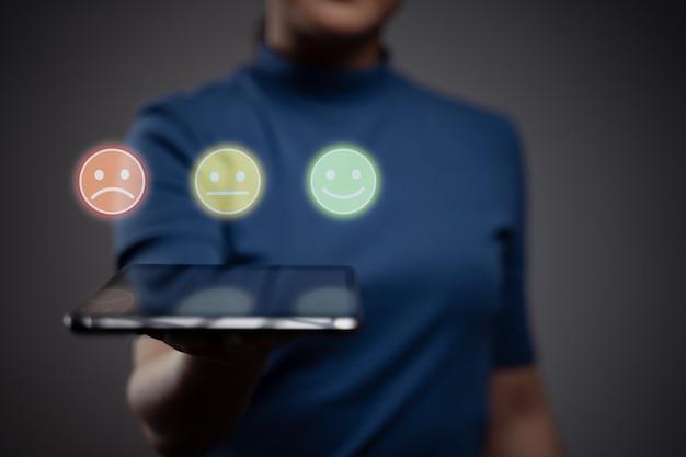 Kobieta trzyma tablet i pokaż efekt hologramu emotikon