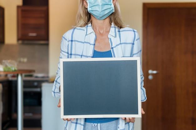 Kobieta trzyma tablicę w domu w rękawiczkach