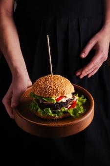 Kobieta trzyma talerz z hamburgerem