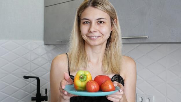 Kobieta trzyma talerz ze świeżymi warzywami i uśmiechnięty