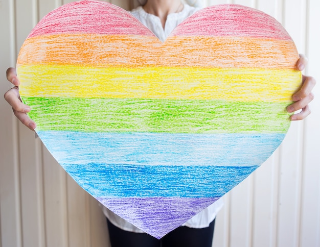 Kobieta trzyma tęczowe serce na białej ścianie symbol społeczności lgbt