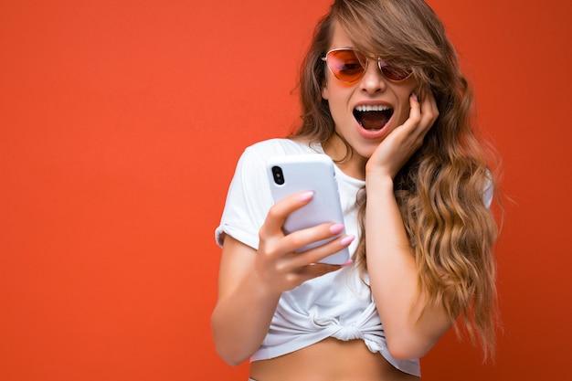 Kobieta trzyma telefon komórkowy nosi okulary codzienny stylowy strój na białym tle na tle ściany