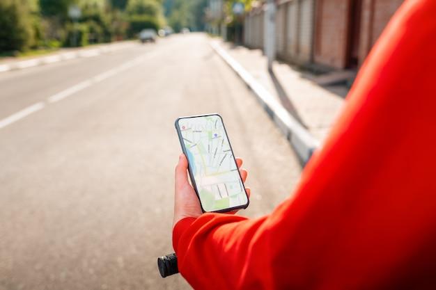 Kobieta trzyma telefon komórkowy z aplikacją mapy online