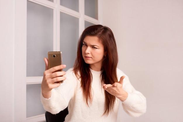 Kobieta trzyma telefon rozmawiając o problemach skoncentrowana dziewczyna za pomocą smartfona