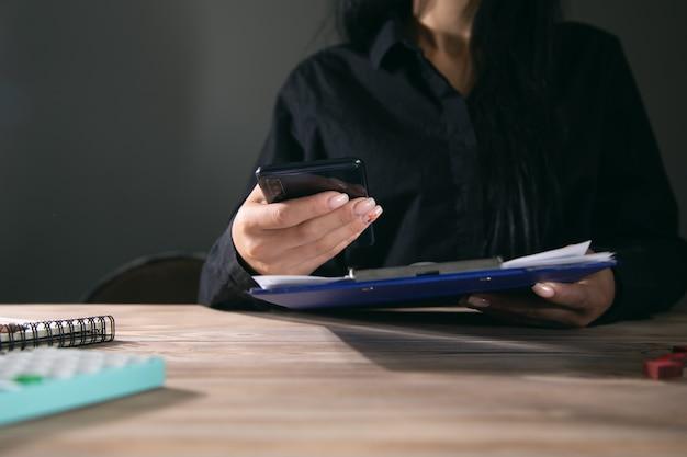 Kobieta trzyma telefon z dokumentami na biurku