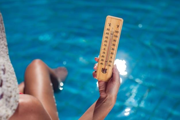Kobieta trzyma termometr na niebieskim tle basenu. koncepcja upałów i lata