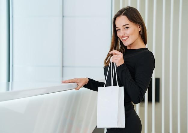 Kobieta trzyma torbę na zakupy na białym tle. biała papierowa torba. nowoczesne biuro tło.