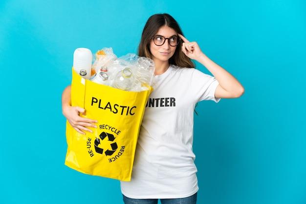 Kobieta trzyma torbę pełną butelek do recyklingu na białym tle na niebieskiej ścianie, mając wątpliwości i myślenie