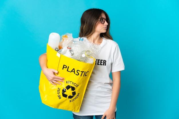 Kobieta trzyma torbę pełną butelek do recyklingu na białym tle na niebieskiej ścianie, patrząc z boku