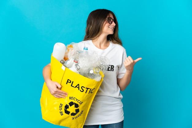 Kobieta trzyma torbę pełną butelek do recyklingu na białym tle na niebieskiej ścianie, wskazując na bok, aby przedstawić produkt