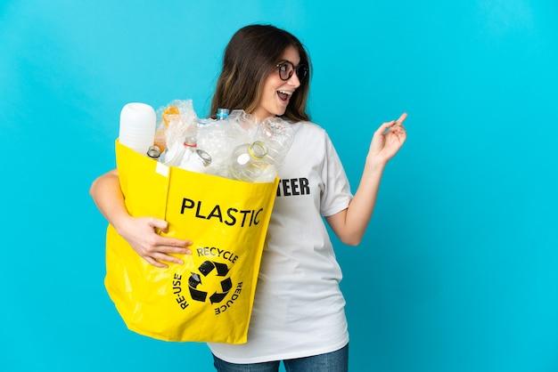 Kobieta trzyma torbę pełną butelek do recyklingu na białym tle na niebieskim tle, wskazując palcem w bok i prezentuje produkt
