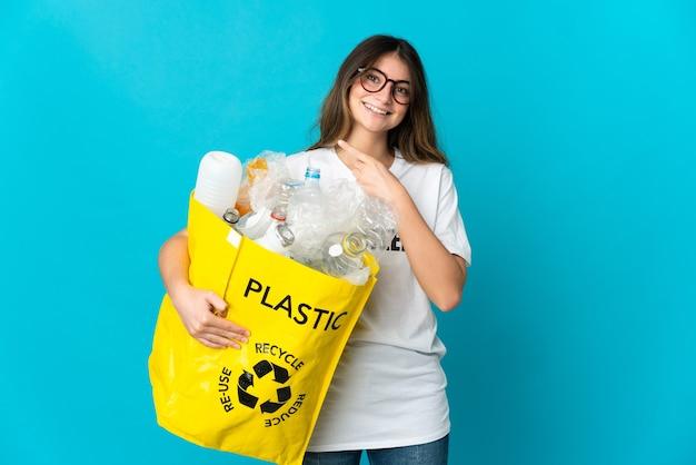 Kobieta trzyma torbę pełną butelek do recyklingu na białym tle na niebiesko, wskazując na bok, aby przedstawić produkt