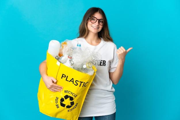 Kobieta trzyma torbę pełną butelek do recyklingu na niebiesko, wskazując na bok, aby zaprezentować produkt