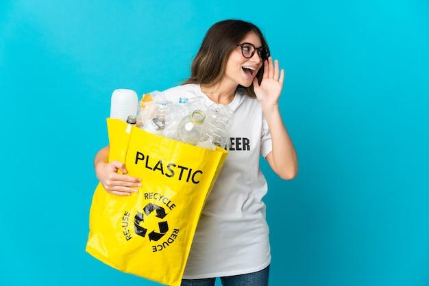 Kobieta trzyma torbę pełną butelek do recyklingu odizolowane na niebiesko, krzycząc z ustami szeroko otwartymi na bok