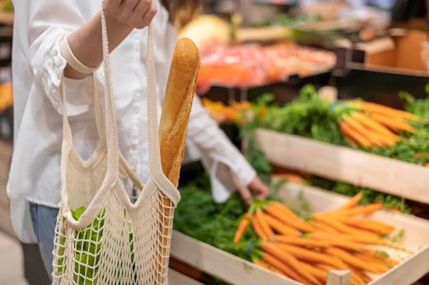 Kobieta trzyma torbę wielokrotnego użytku w sklepie spożywczym