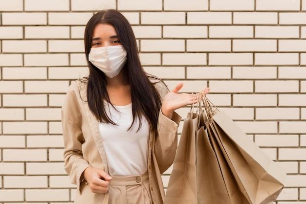 Kobieta trzyma torby na zakupy i ma na sobie maskę