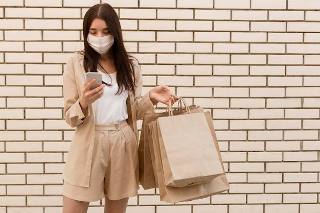 Kobieta trzyma torby na zakupy i noszenie maski widok z przodu