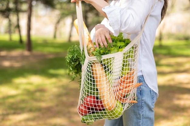 Kobieta trzyma torby wielokrotnego użytku w przyrodzie