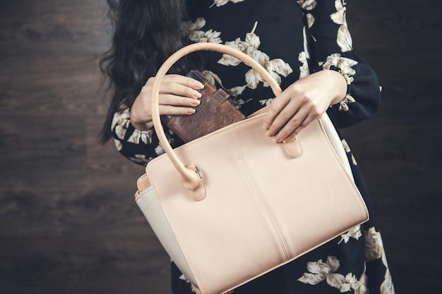 Kobieta trzyma torebkę i portfel w ciemnym pokoju