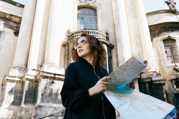 Kobieta trzyma turystyczną mapę w jej ręki pozyci przed starą katedrą
