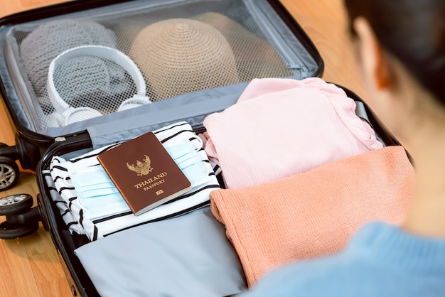 Kobieta trzyma ubrania i paszport z maską w bagażu