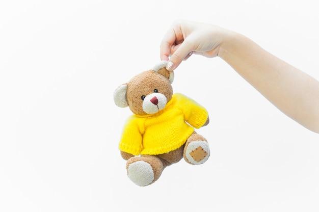 Kobieta trzyma ucho brązowy miś zabawka nosić żółte koszule na białym tle