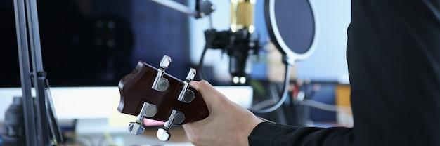 Kobieta trzyma ukulele przed złotym nowoczesnym profesjonalnym mikrofonem