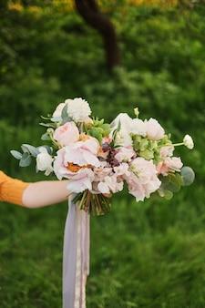 Kobieta trzyma w dłoni piękny bukiet ślubny