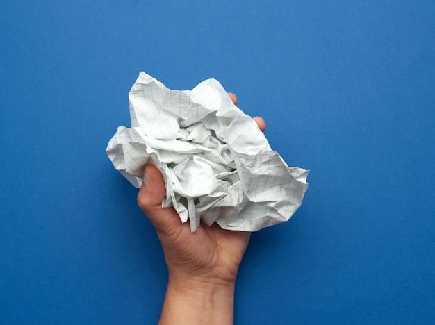 Kobieta trzyma w dłoni pognieciony arkusz papieru w klatce