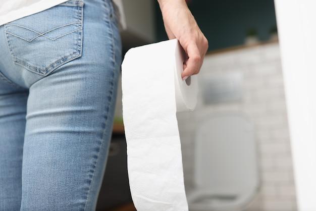 Kobieta trzyma w dłoni rolkę papieru toaletowego, idąc do toalety