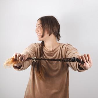 Kobieta trzyma w dłoni ścięty warkocz, który sama obcina.