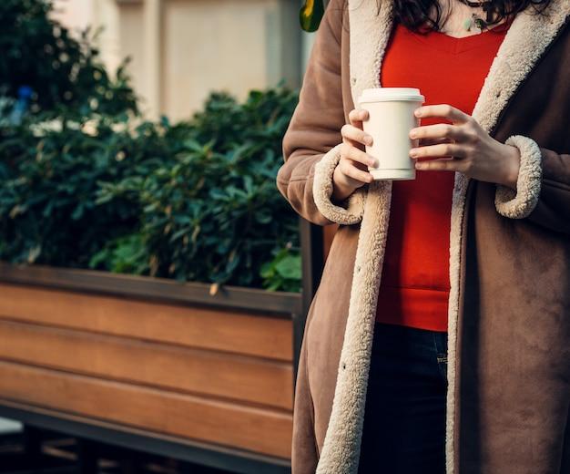 Kobieta trzyma w jej ręce filiżankę kawy