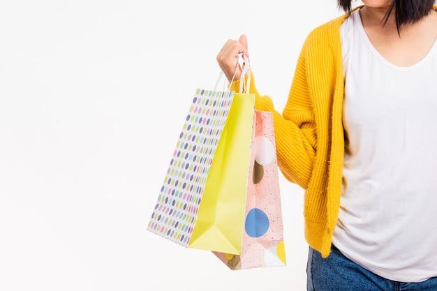 Kobieta trzyma w ramionach wiele kolorowych toreb na zakupy