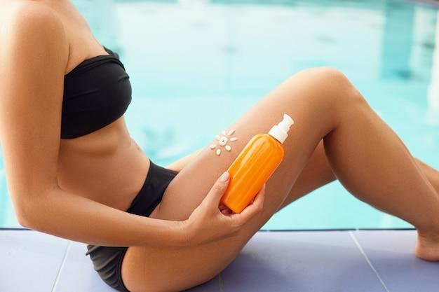 Kobieta trzyma w rękach butelki z filtrem przeciwsłonecznym