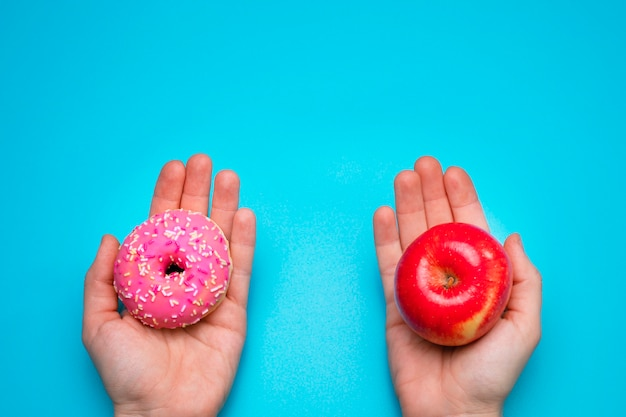 Kobieta trzyma w rękach jabłko i pączek. koncepcja zdrowego stylu życia lub żywienia.