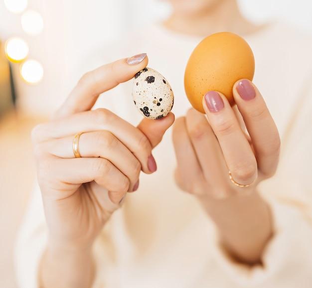 Kobieta trzyma w rękach jajka kurze i przepiórcze. białko w żywności, koncepcja zdrowej żywności, witaminy i składniki odżywcze