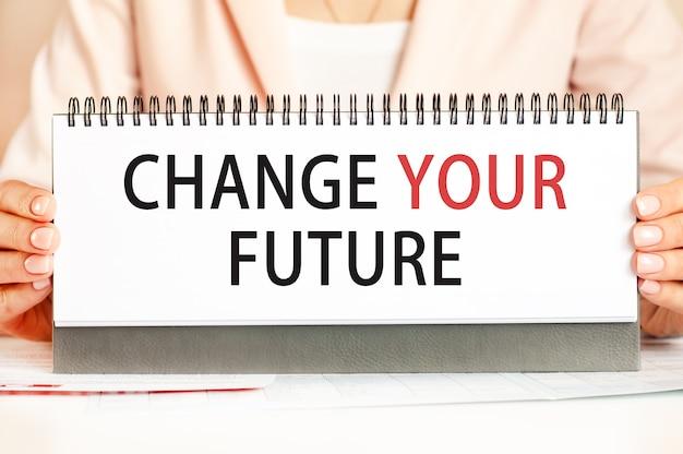 Kobieta trzyma w rękach kartonik z tekstem, który zmieni twoją przyszłość. tekst pisany czarnymi i czerwonymi literami. pomysł na biznes.