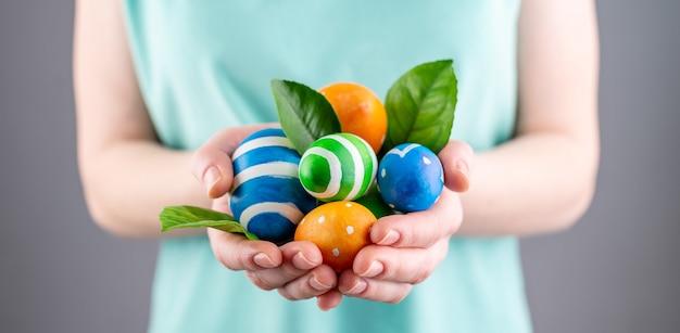 Kobieta trzyma w rękach kolorowe jajka i zielone liście. koncepcja wielkanocy i wiosny. zbliżenie.