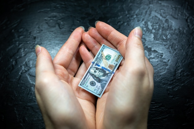 Kobieta trzyma w rękach małego dolara. kryzys gospodarczy w usa. dewaluacja waluty i inflacja.