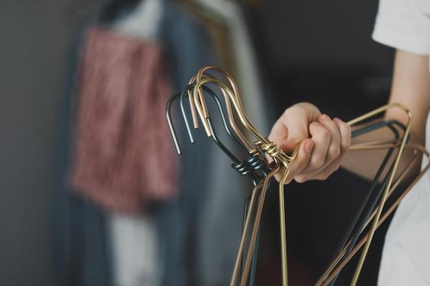 Kobieta trzyma w rękach metalowe wieszaki na ubrania