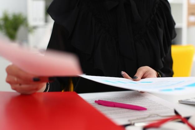 Kobieta trzyma w rękach papiery siedzą przy stole