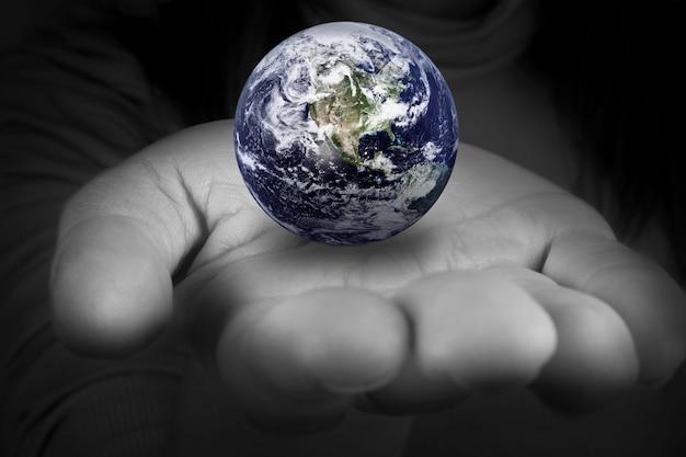 Kobieta trzyma w rękach planetę ziemię. elementy tego obrazu dostarczone przez nasa