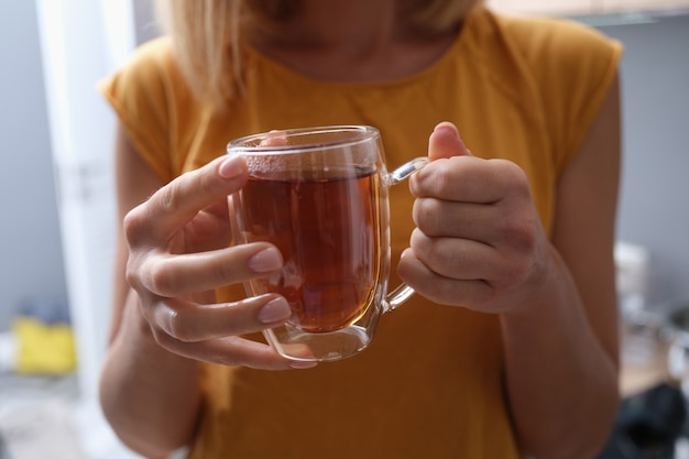 Kobieta trzyma w rękach przezroczystą filiżankę gorącej herbaty
