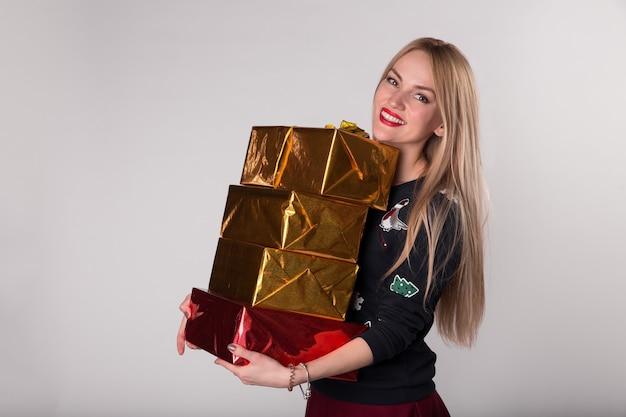Kobieta trzyma w rękach pudełka z prezentami