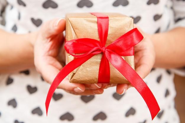 Kobieta trzyma w rękach pudełko przewiązane czerwoną wstążką. płytka głębia ostrości, selektywne skupienie się na polu. koncepcja dawania prezentu na wakacje lub urodziny.